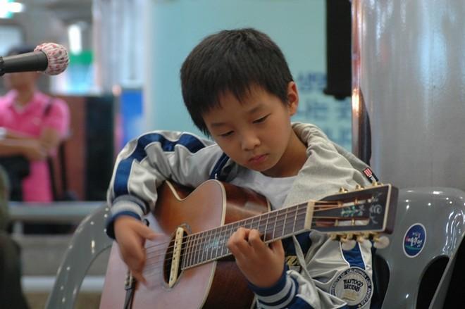 tư thế ngồi chơi đàn guitar của trẻ